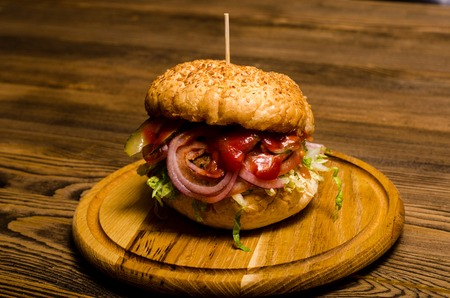 Bacon burger with beef patty on wooden table. Stock Photo