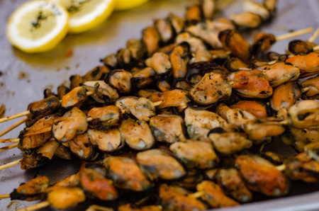Fried mussels with onions on skewers with lemon and parsley