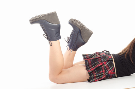 Naked female legs in boots isolated on white.
