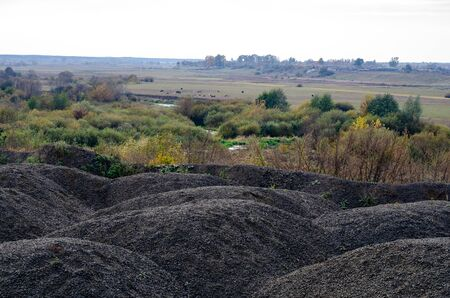 Industrial background with pile of gravel. Extraction of gravel. Construction of roads. Piles of gravel on construction site