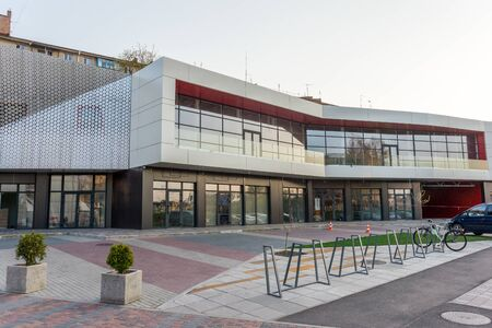 details of aluminum facade with colorful red and orange panels on large shopping mall.