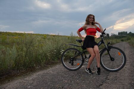 Beautiful girl riding bike at fields at sunset.