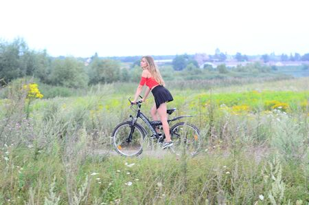 Beautiful girl riding bike at fields at sunset. Ukraine Lutsk 03-08-2017 에디토리얼