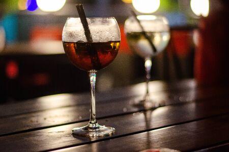 Schöne Reihenlinie von verschiedenfarbigen Alkoholcocktails auf einer Party, Martini, Wodka und anderen auf dekoriertem Catering-Bouquet-Tisch auf Open-Air-Veranstaltung, Bild mit schönem Bokeh.