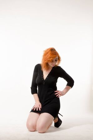 Hermosa chica pelirroja con un vestido negro sobre un fondo blanco. Foto de archivo