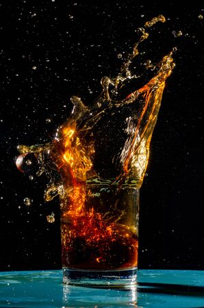 The breaking of a glass with fragments. The explosion of a glass on a black background with a colored liquid. Splashes of colors