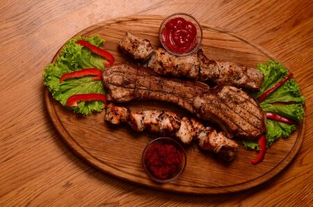 Sliced grilled beef barbecue Striploin steak with chimichurri sauce on cutting board on dark wooden background.