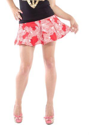 jambes féminines minces portant des talons hauts sur fond gris. corps parfait en body.