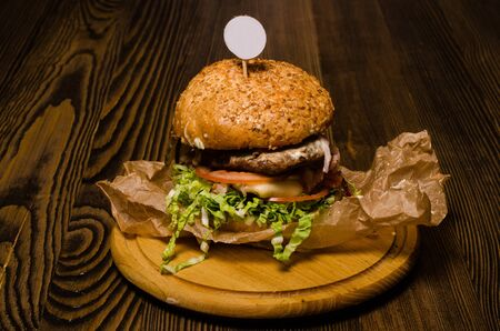 Bacon burger with beef patty on wooden table