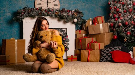 Smiling young woman opening a gift box near beautiful Christmas tree at home. Luxurious Christmas decoration. Presents for Christmas and New Year.
