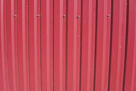 Background striped red metal profile. Texture of painted red metal surface.