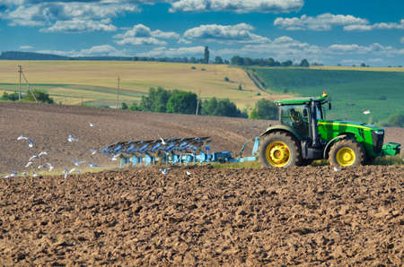 Lutsk Ukraine Farmer in tractor preparing land with seedbed cultivator as part of pre seeding activities in early spring season of agricultural works at farmlands. 10.07.2017