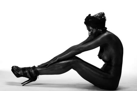 Naked woman painted in black on a white background in the studio