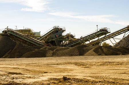 Mobile Stone crusher machine by the construction site or mining quarry for crushing old concrete slabs into gravel and subsequent cement production. Stock Photo