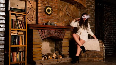 Mysterious brunette girl in red dress and lace mask, sitting by fireplace.