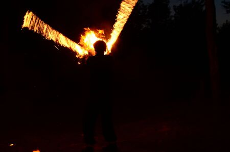 fire show, dancing with flame, male master fakir with fire works, performance outdoors, flame control man, a man in a suit LED dances with fire, draws a fiery figure in the dark.