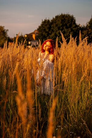red-haired beautiful girl sits with her back in black, long dress in the grass.