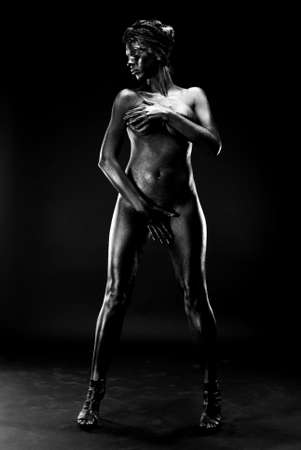 Naked woman painted in black on a white background in the studio. Foto de archivo