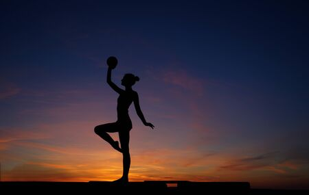 dancer in the dance does the splits in the air against the sunset.