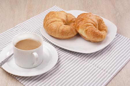 Breakfast croissant and coffee on wooden Reklamní fotografie