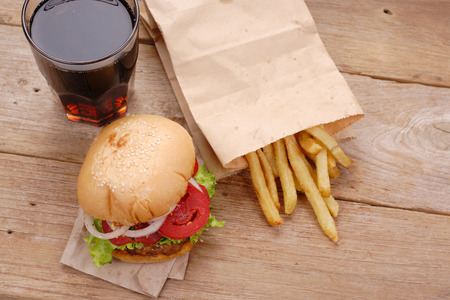edibles: hamburger and french fries on wooden background