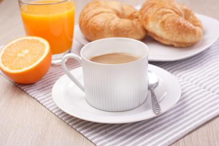 Breakfast coffee and orange juice on wooden