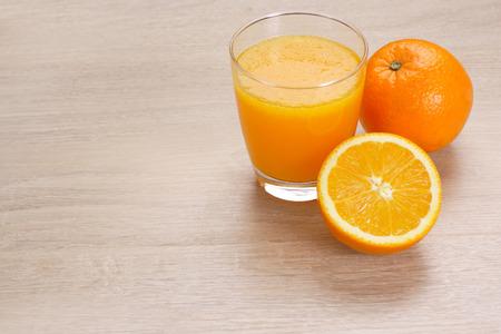 Orange juice with Oranges on wooden background
