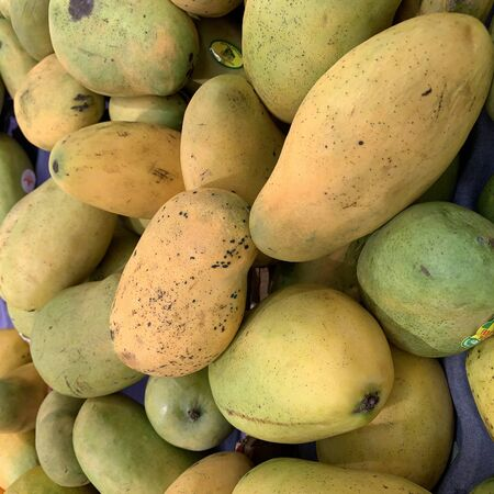 photo of a set of ripe mangoes on a wooden platform