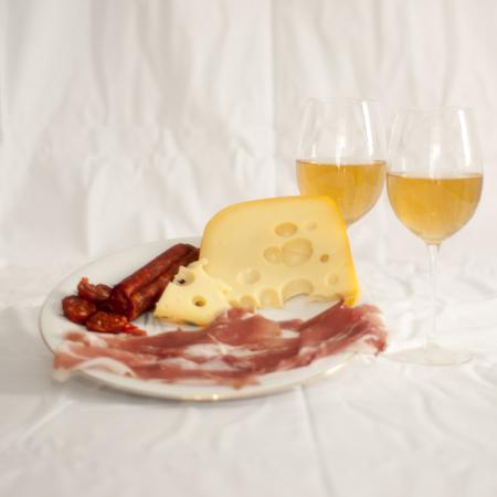 carnes: Plato de carnes y quesos de aperitivo, con dos copas de vino surgi� con el vino blanco en el pa�o blanco Foto de archivo
