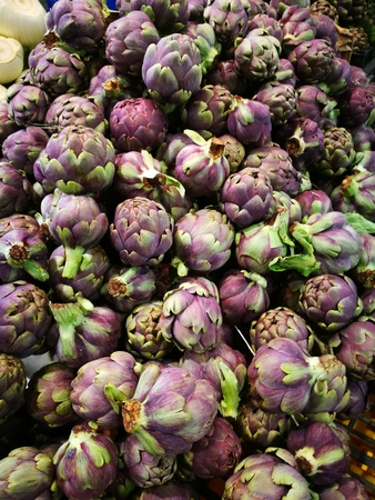 Fresh artichokes with leaves in heap on display on a white background.