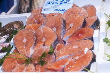 Display of salmon steaks in fish market.