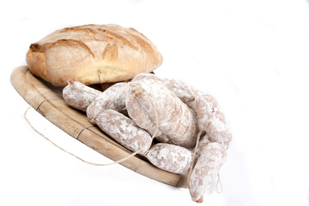 Link sausages with loaf of fresh baked bread on wooden cutting board isolated on white with copy space.