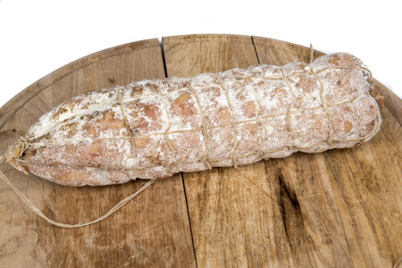 A loaf of bread with a string of dried sausages on a wooden plate.