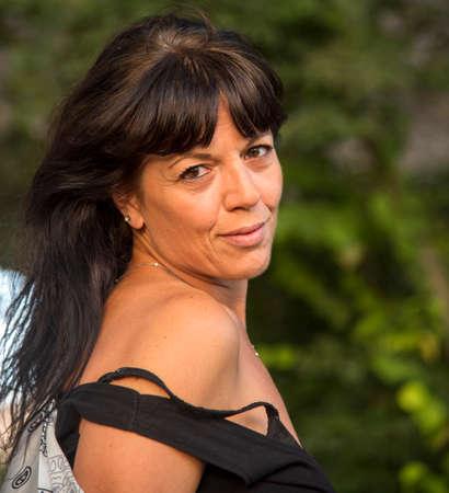 Beautiful Italian girl at the park, wearing a dress