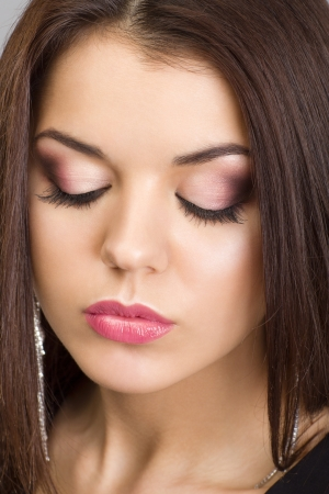 Portrait of a beautiful woman with evening make-up and earrings photo