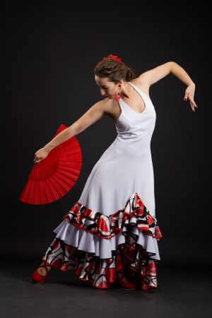 Flamenco dancer in white dress with red fan photo