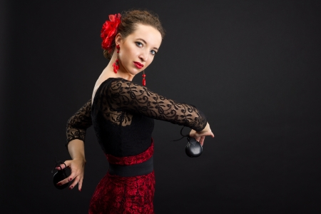 Professional flamenco dancer in black and red dress with castanets photo
