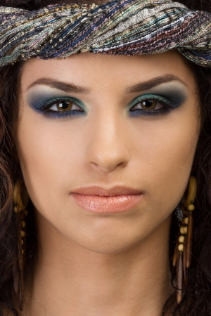 Portrait of young asian woman with wooden earrings and a blue scarf around her head photo