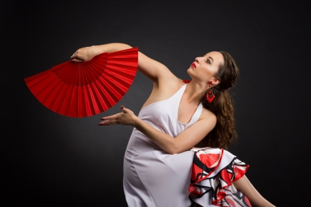 Flamenco dancer in white and red dress with red fan over black background photo