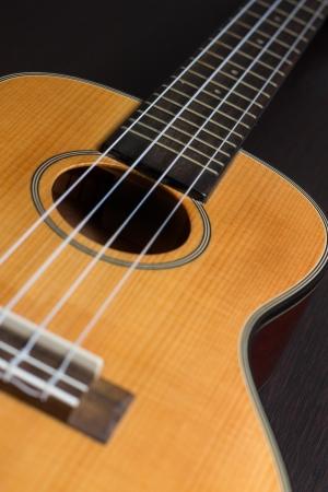 Ukulele hawaiian guitar over dark background  Focus on sound hole  photo