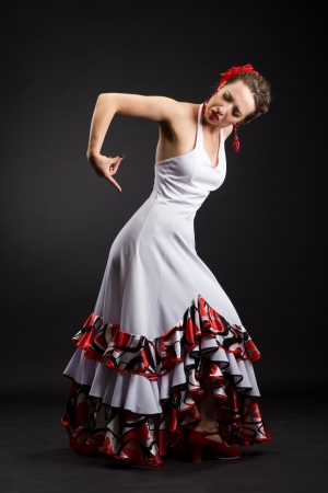 Flamenco dancer in white dress with red earrings over dark background photo
