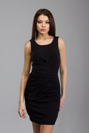 black dress: Beautiful woman standing in a black dress over gray background