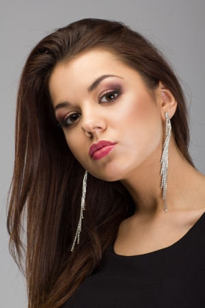 Portrait of a beautiful brunette woman with evening make-up and long earrings photo