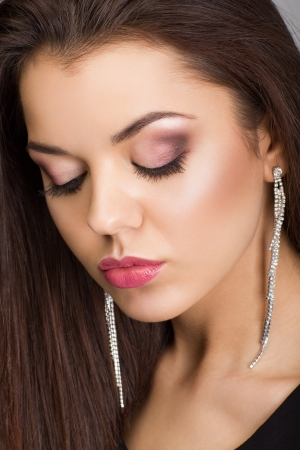 Portrait of a beautiful woman with evening make-up and earrings looking down photo