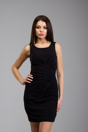 Beautiful woman standing in a black dress over gray background photo