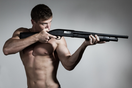 Young  handsome soldier aims a gun photo