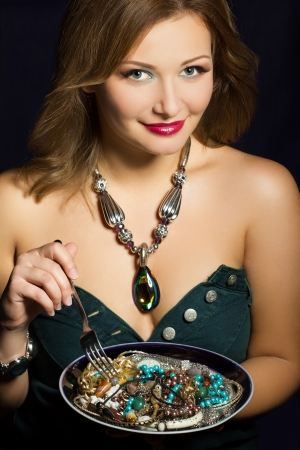 Young woman holding fork and plate with  jewelry photo