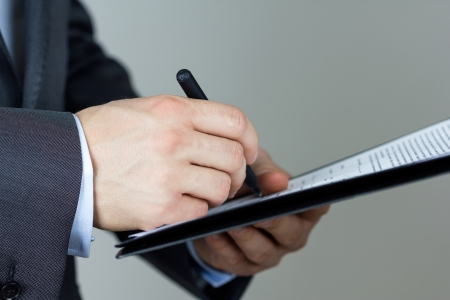 Close-up of business man signing documents