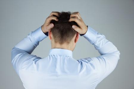 Stressed zakenman met hoofdpijn staat terug naar camera