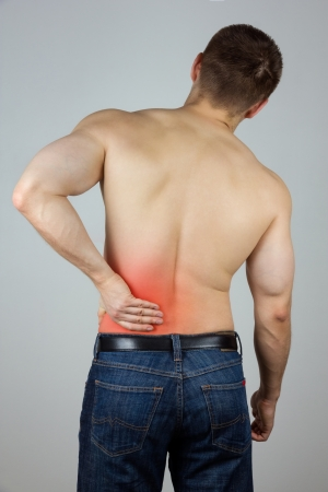 Young man with back pain in the red zone photo
